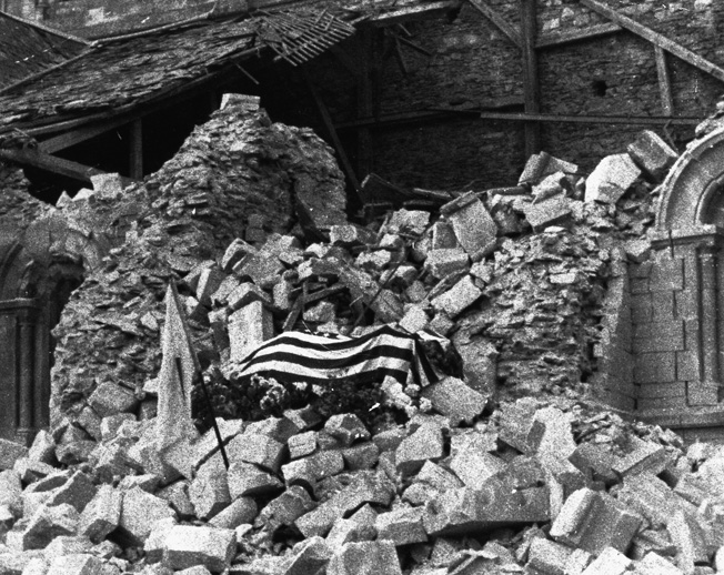 His body draped with an American flag, Major Thomas D. Howie lies in state atop the rubble of a blasted church in the heart of St. Lô.