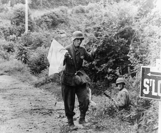 With an American soldier covering his movement, a German soldier surrenders to U.S. forces outside St. Lô.