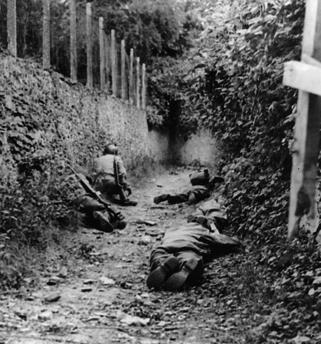 Crouching low against a wall and the eastern mound of a French hedgerow, U.S. soldiers attempt to avoid German artillery fire overhead.
