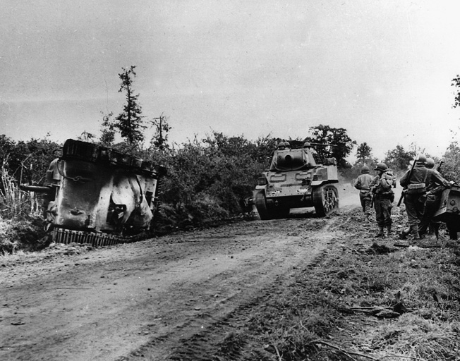Passing the charred remains of one of its own, a U.S. Stuart light tank makes its way down a dusty road toward St. Lô.