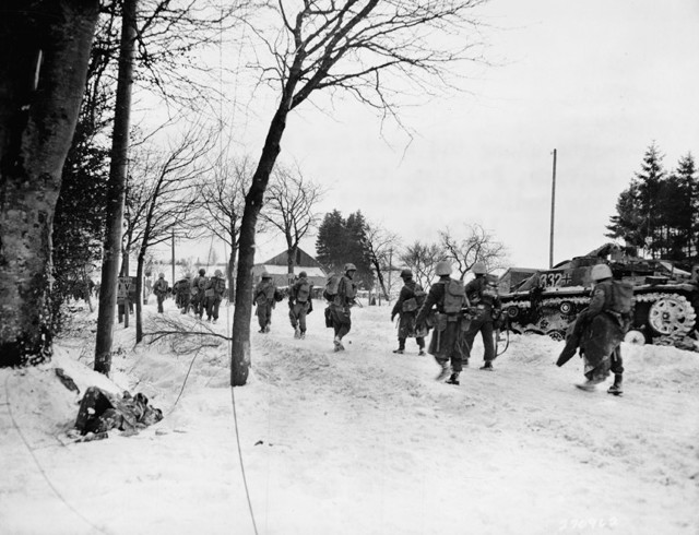 American infantrymen of the 30th Division march down a country lane somewhere in Belgium. Nearby lies the body of a dead German soldier, while several destroyed German tanks bear mute testimony to the ferocity of a recent engagement.