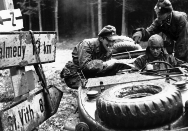 German soldiers of SS Kampfgruppe Peiper pause beside a road sign pointing toward the village of Malmedy during the opening hours of Hitler's desperate Ardennes offensive. Peiper's spearhead was stopped in its drive for the River Meuse by determined resistance from the 740th Tank Battalion at Stoumont, Belgium.
