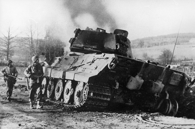 American soldiers gaze at the hulk of a German Tiger tank knocked out near La Gleize during the final stage of the Battle of the Bulge. The fate of the German Ardennes offensive was sealed when the U.S. 740th Tank Battalion stopped Kampfgruppe Peiper at Stoumont.