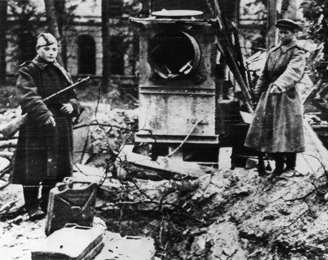 Two Russian soldiers motion towards the place in the Führerbunker garden where the bodies of Hitler and Eva Braun were doused with gasoline and set afire.