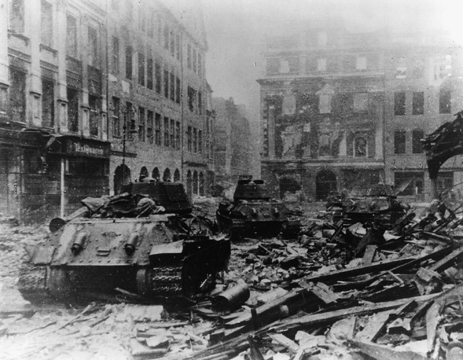 Soviet T-34 tanks rumble through the rubble-strewn streets of Berlin in May 1945.