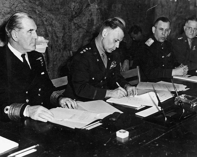 Lt. Gen. Walter Bedell Smith signs surrender papers for General Dwight Eisenhower.