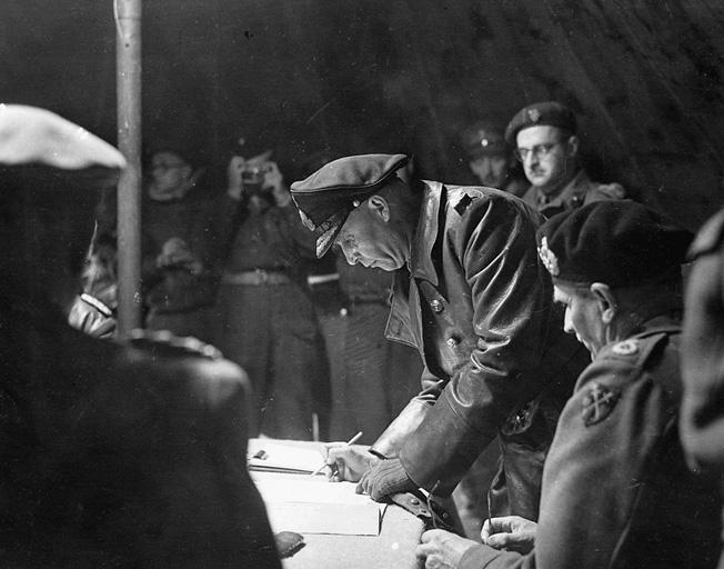 Colonel Johannes Blaskowitz signs formal surrender papers.