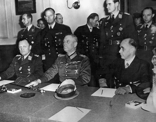 Col. Gen. P.F. Stampf and Field Marshal Wilhelm Keitel sign surrender papers at Russian headquarters in Berlin.