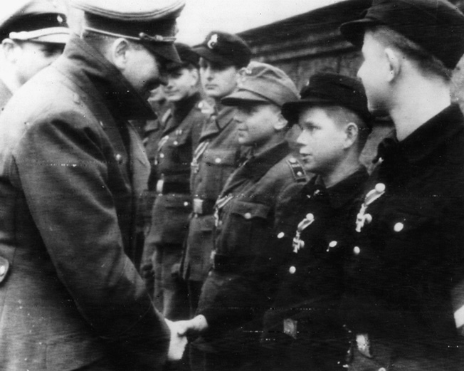 In one of the last known photographs of Hitler, the Führer pins the Iron Cross to the chest of a young boy. The boy, and others like him were virtually all that remained to defend the Fatherland.
