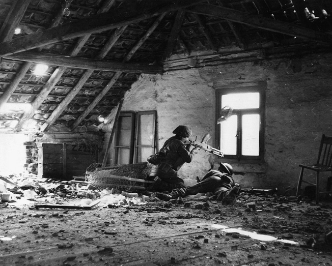 From a window above the streets of a German town, two British soldiers utilizing a Bren gun support comrades below.