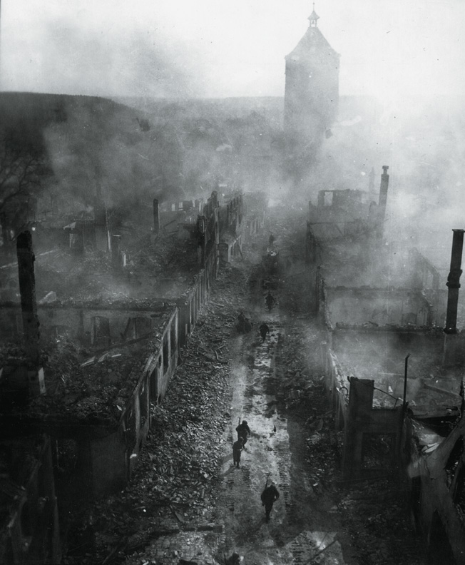 In this eerily surreal image, soldiers of the 225th Infantry Regiment walk down a crowded street in war-torn Waldenburg, Germany. During the final weeks of the war, Allied troops saw firsthand the devastation their war machine had visited upon the enemy.