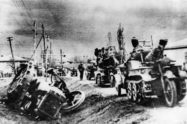 Mounted on kettenkrad caterpillar-powered motorcycles, German soldiers fall back along a dirt road in the Caucasus. After giving up the Taman Peninsula, the Germans attempted to minimize their losses during the retreat.