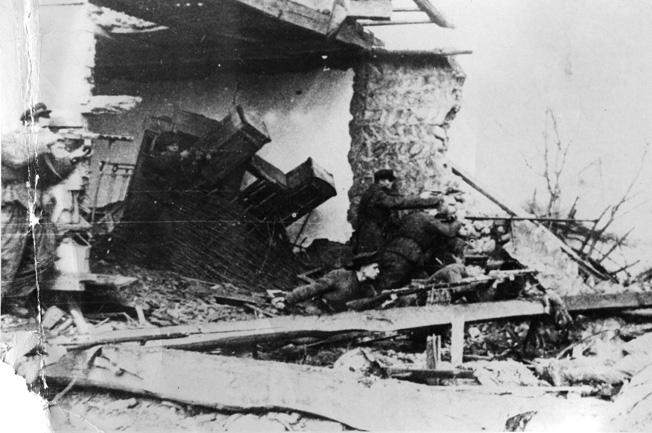 Red Army soldiers take cover behind a mound of debris during their pursuit of retreating German troops after liberating the Taman Peninsula. The victory on the Taman Peninsula was a costly affair for the Soviets during the autumn of 1943.