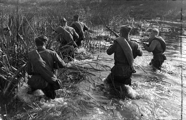 In September 1944, Red Army soldiers wade through a marshy area during a patrol. Such terrain played an important role on the Taman Peninsula as both armies had to contend with mobility issues.