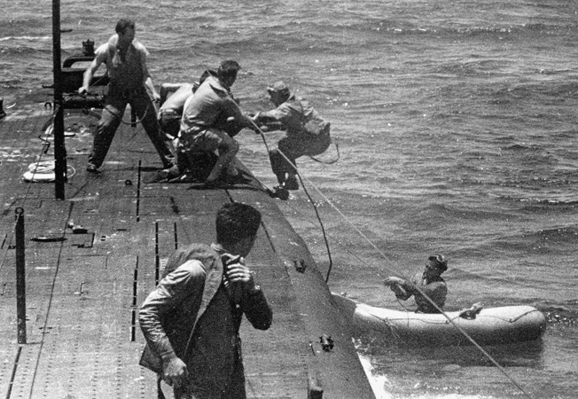 Downed pilots are pulled aboard the USS Tang.