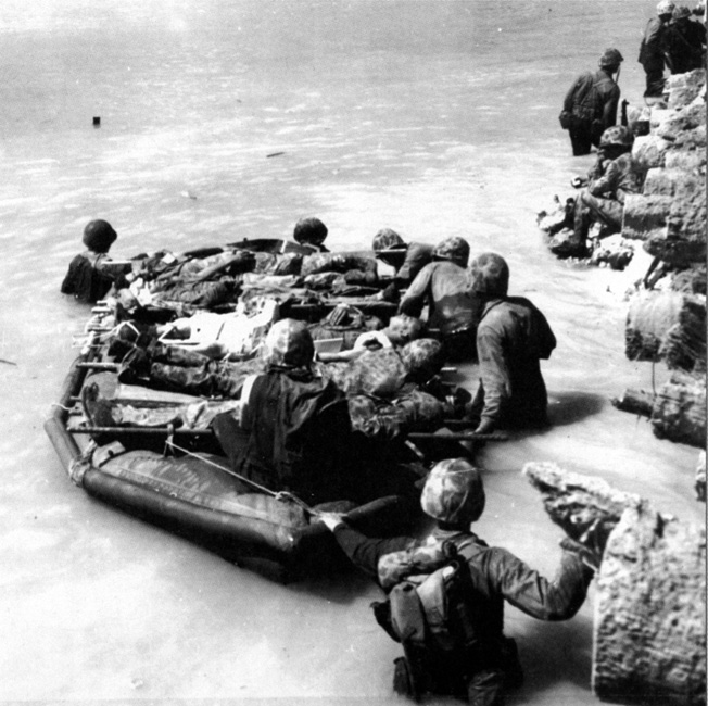 Wounded Marines lie on an assault raft while being ferried along a pier to waiting landing craft. Due to the difficulties of getting wounded men to safety in a timely manner, many died before they could receive comprehensive treatment.