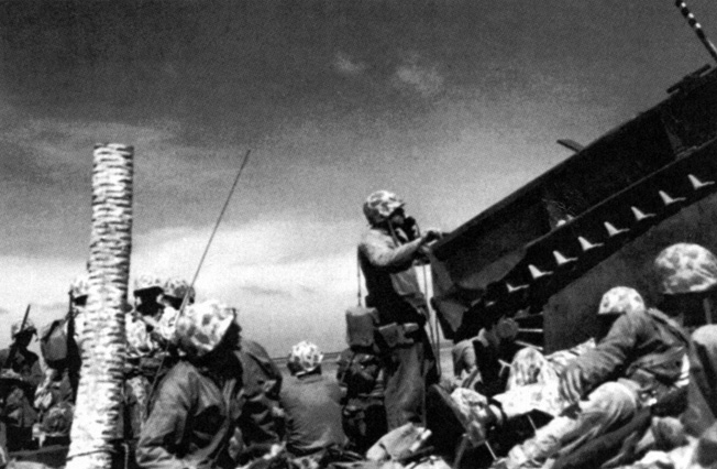 Using a field telephone, Marine Major Jim Crowe shelters behind LVT-23 and directs tactical movements against Japanese positions at Tarawa.