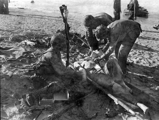 With a bottle of blood plasma positions on a butt of an upended rifle, a Marine receives a life-saving blood transfusion on the beach at Tarawa.