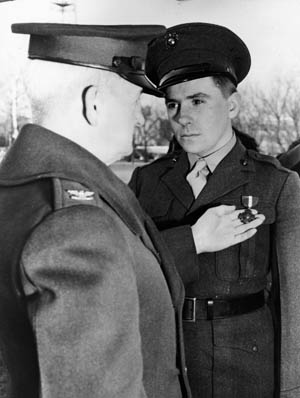 In recognition of his heroism during the fighting at the Tenaru River, U.S. Marine Gunnery Sergeant Al Schmid receives the Navy Cross from Colonel A.E. Randall at the Philadelphia Navy Yard.