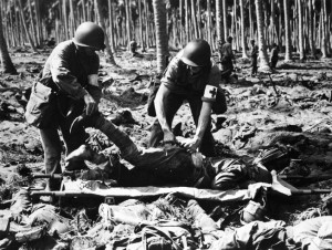 Placing a wounded Japanese soldier on a stretcher, two U.S. Marines have plucked the injured man from among the bodies of his dead comrades. The suicidal charge of the Ichiki Detachment at the Tenaru River took a heavy toll among the elite troops.