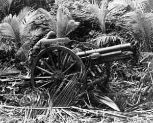 A U.S. soldier examines an antiquated Japanese field artillery piece abandoned during the evacuation of enemy troops from Guadalcanal. The campaign for control of the island also involved several major naval battles.