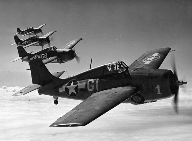A formation of Grumman F4F Wildcat fighter planes banks slowly to the right. Wildcats flown by U.S. Marine Corps aviators based at Henderson Field on Guadalcanal were instrumental in maintaining daylight air superiority and securing the island.