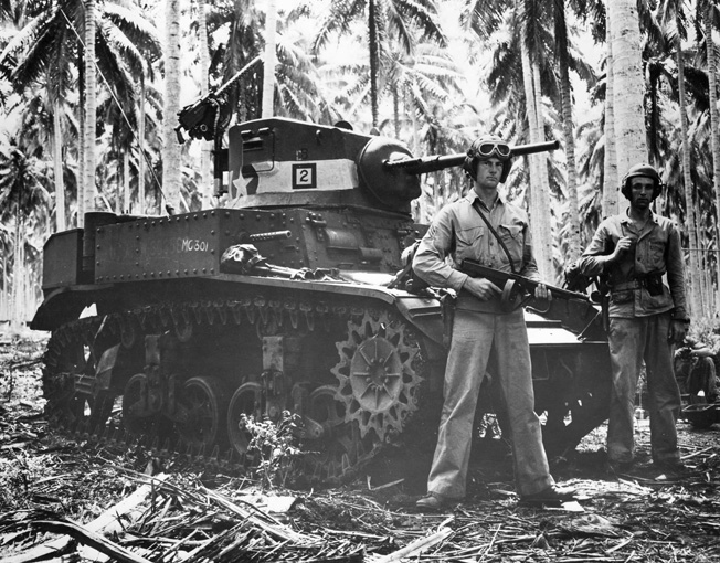 Two American tankers, one of them holding a Thompson submachine gun, stand beside their stuart light tank, which had recently participated in the fighting at the Tenaru River. U.S. firepower, particularly tanks and artillery, played a pivotal role in the victory on the island.