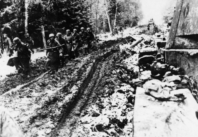 German soldiers are seen struggling to advance along a Russian road that has been turned into a sea of sticky mud by the winter thaw. German men and equipment were severely tested by the elements on the Eastern Front as well as by the Red Army.