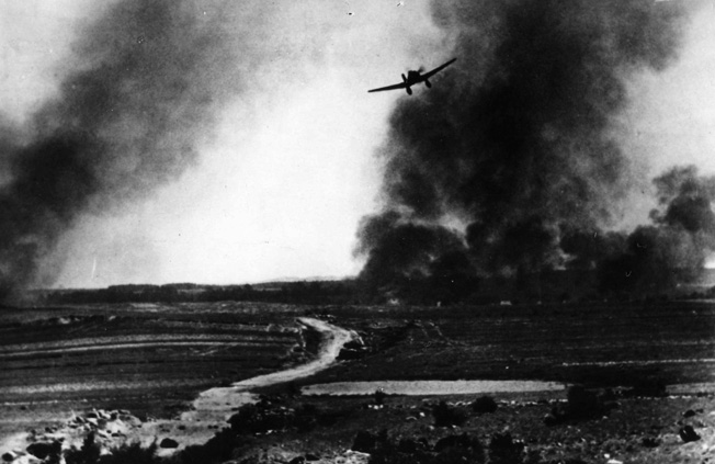 Photographed from the ground, a German Ju-87 Stuka dive-bomber pulls out of its dive against a Red Army tank on the Eastern Front. A number of Stukas were later armed with tank-busting 37mm cannon under the wings.