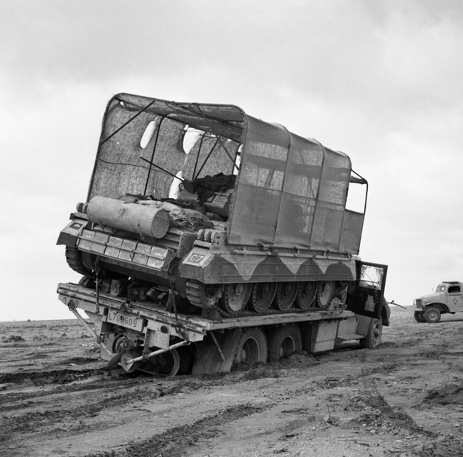 The driver of a British flatbed truck attempts to negotiate the desert sands in March 1942 carrying a Crusader tank covered by the innovative sunshield.