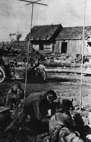 Taking cover during operations against partisans in Russia, Brandenburg commandos prepare to open fire with automatic weapons against an unseen enemy.