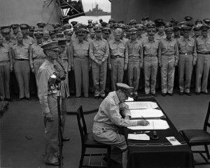 Lt. Gen. Jonathan M. Wainwright and British General Arthur Percival watch as General Douglas MacArthur signs the instrument of surrender in Tokyo Bay on September 2, 1945.