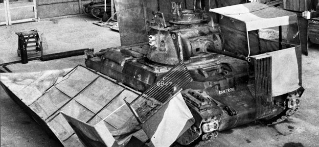 Located at Helwan, Egypt, the Middle East Command Camouflage Development and Training Center was a think tank and laboratory for the deception efforts of A Force. Taken in 1941, this photo shows a British tank with its sunshield split during vehicle servicing on the workshop floor.