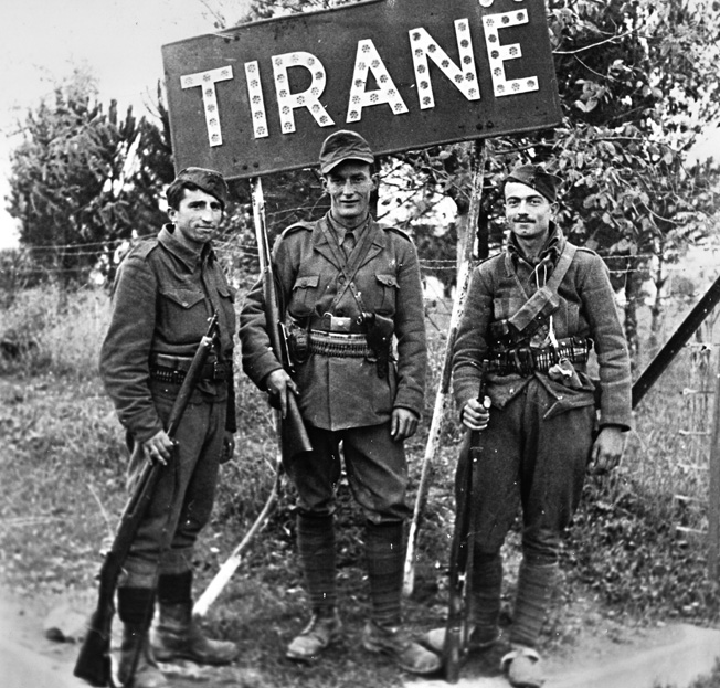 On November 28, 1944, the day Nazi rule ended in Albania, these guerrilla fighters pose under a sign that identifies their hometown. British efforts, led by the Special Operations Executive (SOE), to influence guerrilla operations in Albania met with only partial success at best.