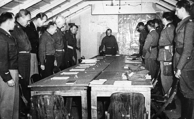 Seated on the right side of the large table, five high-ranking German officers representing General Heinrich von Vietinghoff headquarters in northern Italy to discuss logistical issues related to the surrender of German forces.