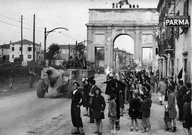 The citizens of Parma in northern Italy line the streets to cheer the advancing Allied columns pursuing the retreating Germans. Here, a towed 155mm howitzer makes its way down the street amid the gathering of well wishers.
