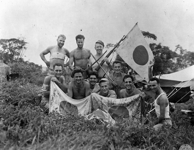 A triumphant group of American soldiers displays trophies of war taken from the vanquished Japanese during a recent engagement near Kamaing, Burma.
