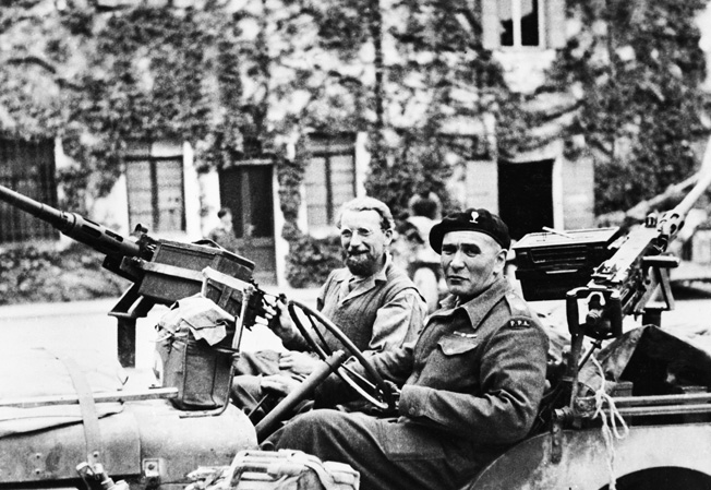 Lieutenant Colonel Vladimir Peniakoff, known as Popski, sits behind the wheel of a jeep with his gunner, Corporal Ron Cokes, at the University of Padua in Italy in May 1945. Note that Popski utilizes a hook after losing his left hand in combat.