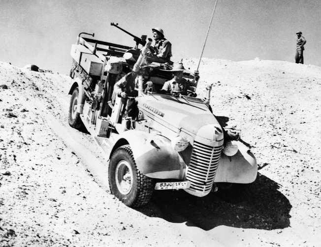 On patrol in the desert in March 1941, a truck of the Long Range Desert Group traverses a sand dune.