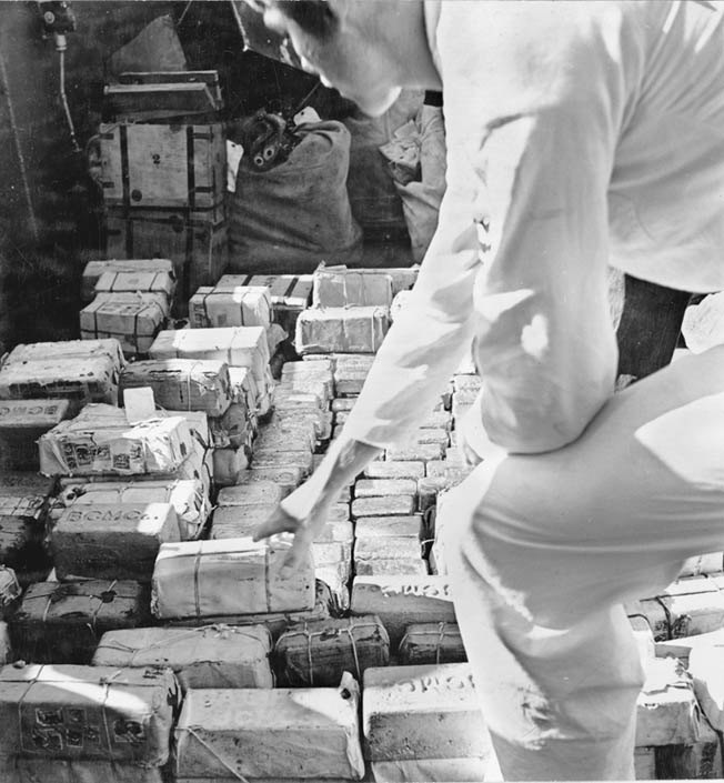 Sailors aboard the submarine USS Trout reach for bundles of currency and bars of gold formerly residing in the Philippine Treasury. In the spring of 1942, the valuable treasure was removed from Manila, the capital city of the Philippines, to prevent its falling into the hands of the Japanese.