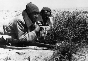 Keeping alert to report enemy movements, a tow-man LRDG team remains concealed behind Axis lines.