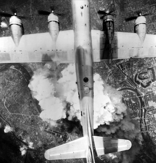 A U.S. B-29 Superfortress heavy bomber rains destruction on a Japanese city as billowing smoke from the bombs dropped earlier rises upward.