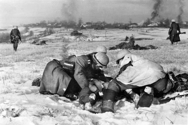 After the easy victories in the summer of 1941, the Germans met increasing resistance the farther into the Soviet Union they pushed. Here, with a light dusting of snow on the ground, German troops assist a fallen comrade while tanks and infantry advance toward a burning village.