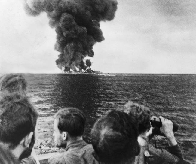 Crewmen of a German U-boat watch a blazing tanker burn to the waterline after their torpedo attack. During Operation Drumbeat, U-boats ranged along the U.S. East Coast, attacking merchant shipping with impunity.