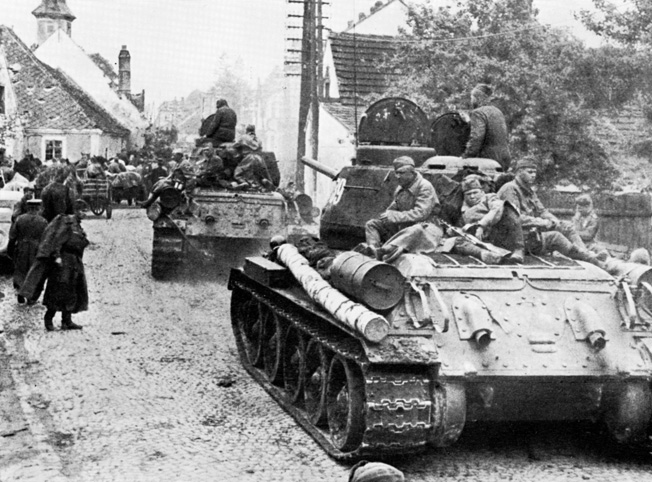 Advancing steadily westward, Soviet soldiers ride atop T-34/85 medium tanks as their column rolls through an Austrian village in the waning days of the war in Europe.