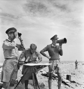 Manning the command post of the Royal Horse Artillery, officers use a map, megaphone, and field glasses to assess and redirect the accuracy of their fire against advancing Italian troops and tanks. The troop commander, left, is spotting the fall of the shells, while the gun position officer, right, gives the order to fire the heavy guns.