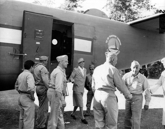 Major General Maxwell Murray (left) and Admiral Aubrey Fitch greet one another as they prepare to welcome First Lady Eleanor Roosevelt, exiting the aircraft, to Espiritu Santo in the New Hebrides, 1942.