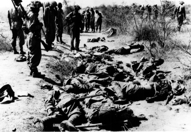 The cost of an unsuccessful counterattack at Meiktila is apparent as British soldiers view scores of dead enemy troops.