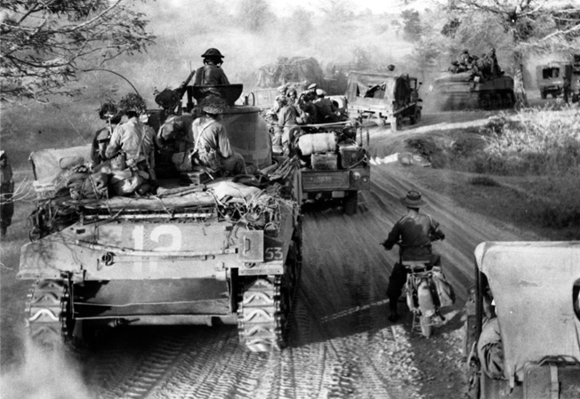 Advancing one the road between Myaungyu on the Irrawaddy River and Meiktila, Sherman tanks and vehicles of the British 62nd Motorized Brigade keep a strenuous pace, March 1945.