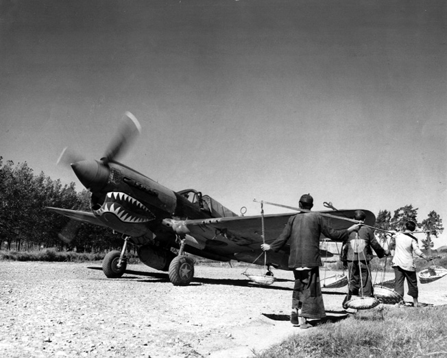 A P-40 of the legendary Flying Tigers prepares for takeoff from an airfield in a remote part of China.